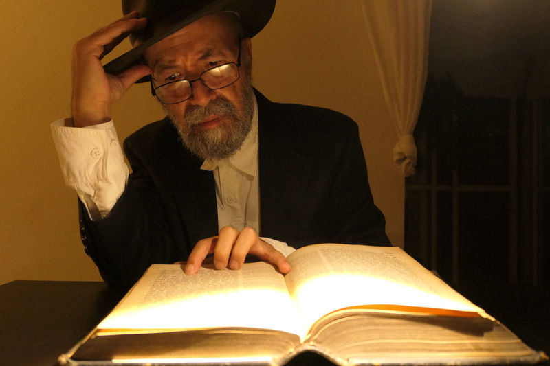 Midsection of man reading book