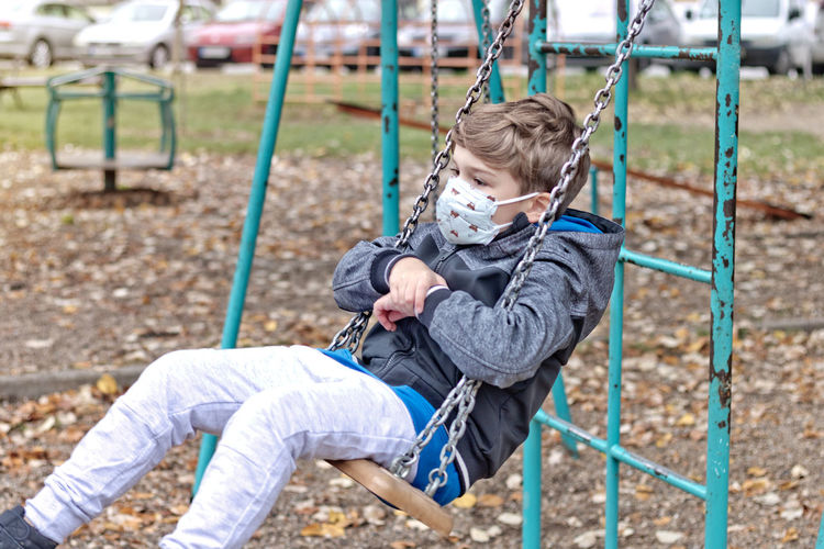 Lonely kid wit protective face mask swinging on the playground at the park.