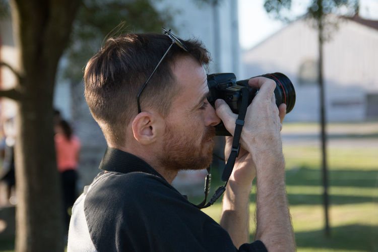 Portrait of man photographing outdoors