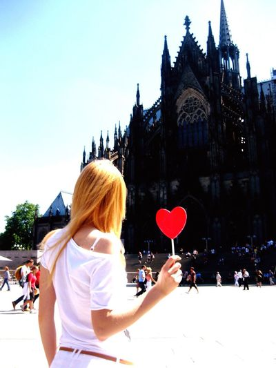 Rear view of woman standing with red heart shape at cologne cathedral