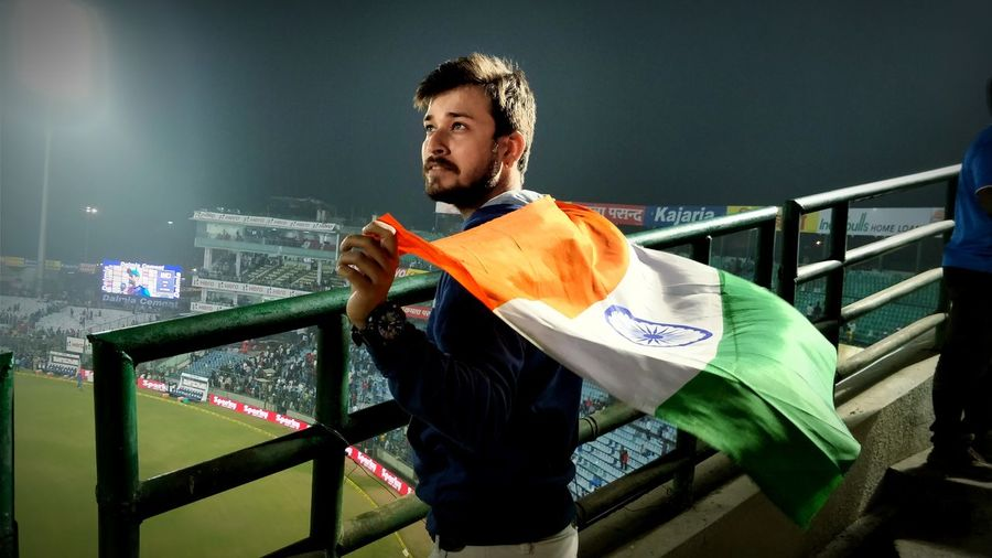 Man holding indian flag while standing at stadium