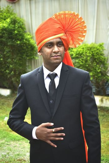 Man in suit wearing orange turban while standing on field