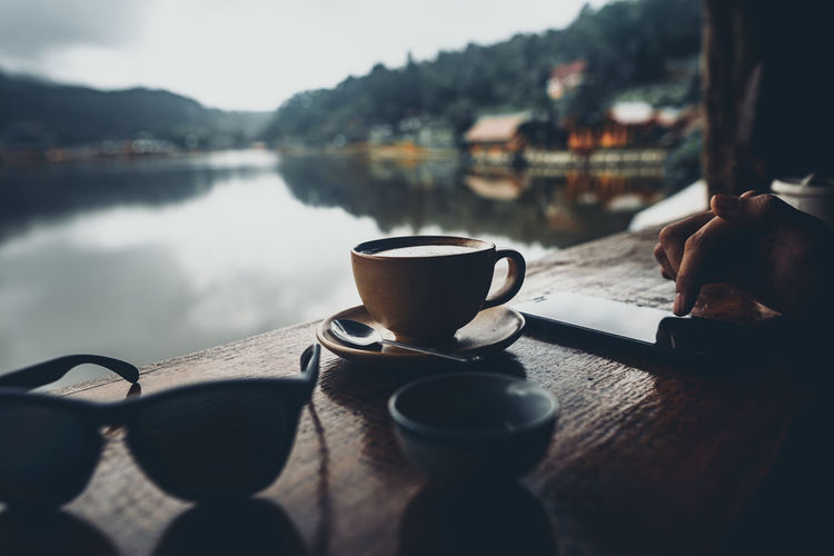 Coffee cup on table by lake