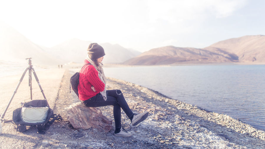 Side view of woman sitting at lakeshore against mountains