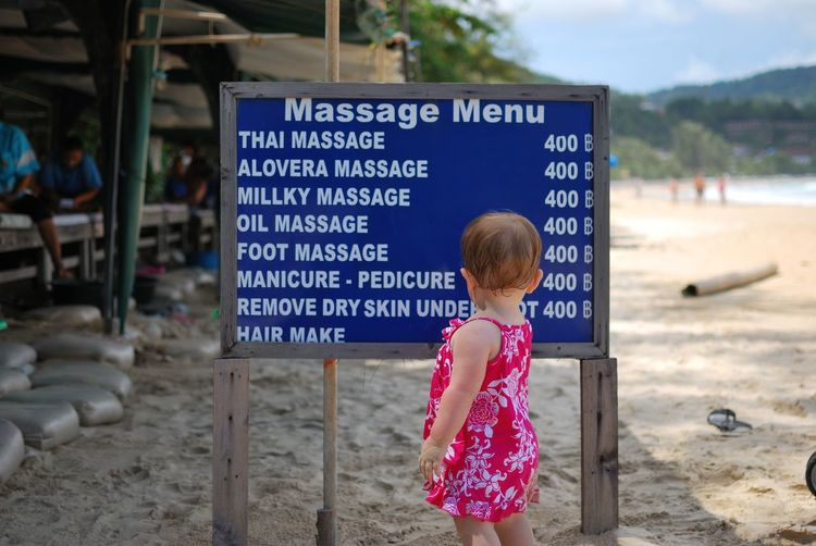 Baby on beach next to sign Beach Childhood Day Massage One Person Outdoors Real People Sand Sign Board Sky Standing Text Thai Sign Vacations