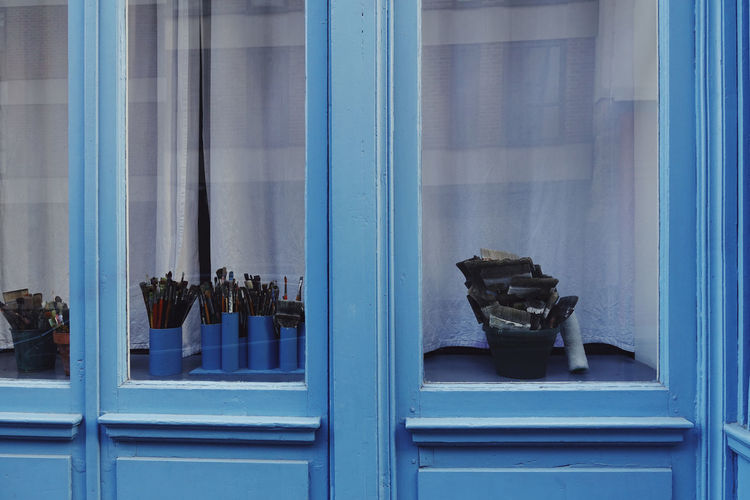 Various Paintbrushes On Table Seem Through Window