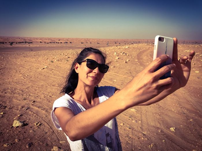 Smiling Woman Taking Selfie Through Mobile Phone While Standing On Field Against Clear Sky