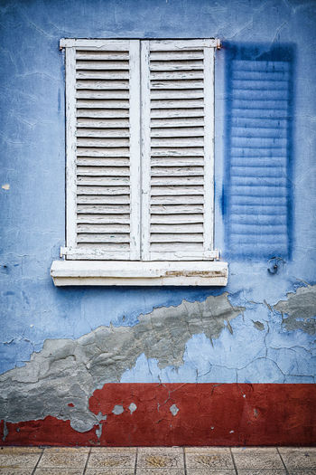 Sun bleached wall with the shadow of the shutter that is most often open etched in Exterior Interesting Pictogram SPAIN Travel Architectural Detail Blinds Blue Blue Wall Bright Sun Exterior Wall Faded Faded Paint Passing Of Time Rough Shutter Sun Bleached Sunshine White Shutters