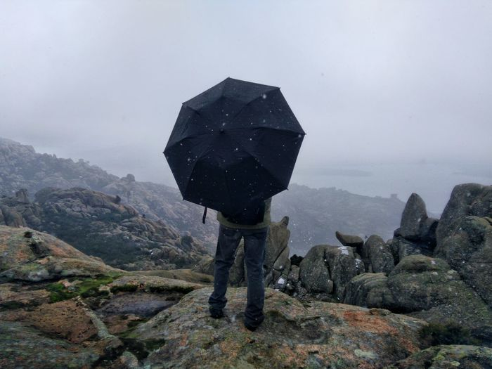 Man with umbrella on a mountain peak with his back to the camera