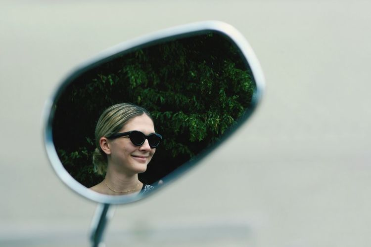 Smiling Woman Reflecting In Side-View Mirror
