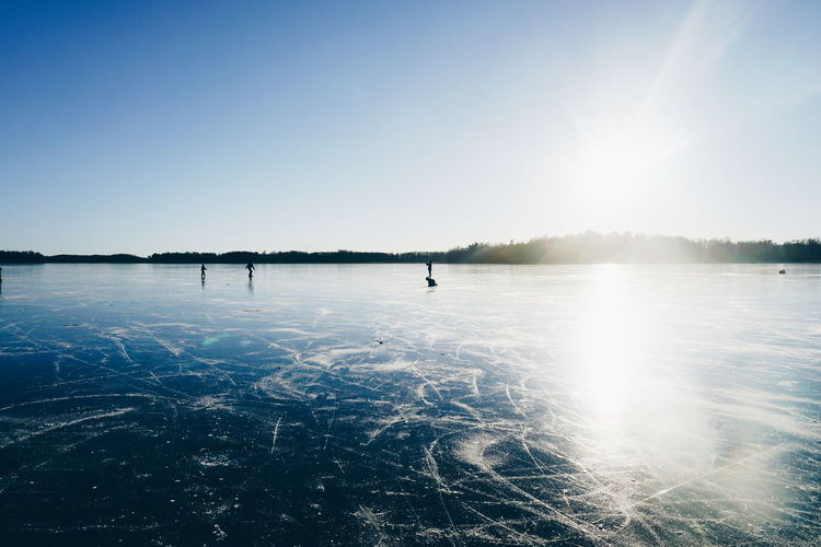People ice-skating on frozen lake against sky on sunny day