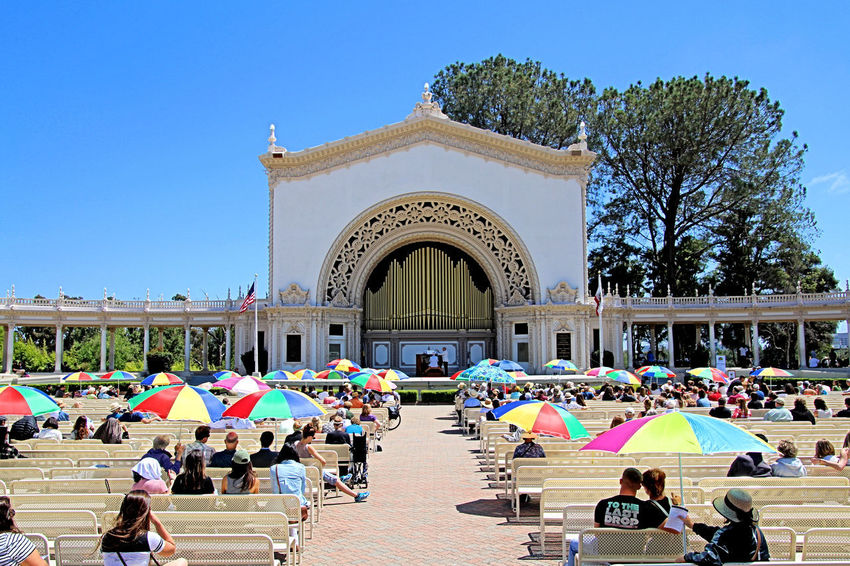 All concerts on the Spreckels Organ are free to the public in accordance with the original Deed of Gift by John and Adolph Spreckels. Concerts are held every Sunday at 2 p.m. for one hour (rain or shine) and on Monday nights comprising the International Summer Organ Festival – concerts take place at 7:30 p.m. on Mondays from late June through the end of August. At least 62 concerts are scheduled during a typical year. The Pavilion seats 2,400 people on plaza benches. Airplanes fly by to land on the nearby International Airport and Trolleys carry visitors throughout the Park. These photos conclude the Organ Concert so let's go see what's happening down on the Bay. Day Organ, Organist, Organ Concert, Organ Pipes, Venue, Pavillion, Pavilion, Balboa Park, San Diego, California, Outdoors Tree Trolley, Umbrellas, Airplane, Promenade, Colonade, Audience, Concert, Pavillion, Pavilion, Music,