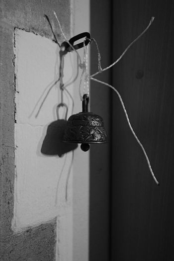 Bell hanging on wall of abandoned house