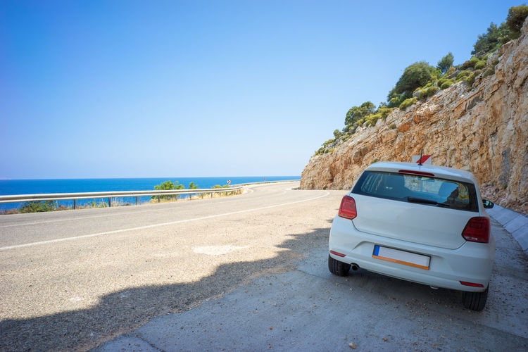A white passenger car is parking in shade on Road D400, the famous self-driving route in Turkey for tourist, by dark blue Aegean Sea under blue sky in summer. Aegean Attraction Blue Car D400 Drive Hill Kas Mountains Parking Rental Car Resting Road Route Self-driving Car Shade Shadow Sky Summer Tourism Travel Turkey Visit Water White