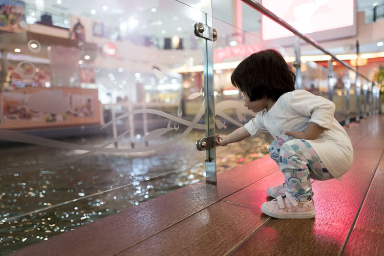 Girl Holding Glass Knob While Crouching In Shopping Mall