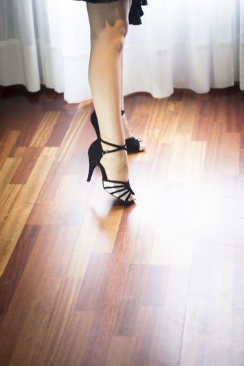 Low section of woman standing on parquet floor
