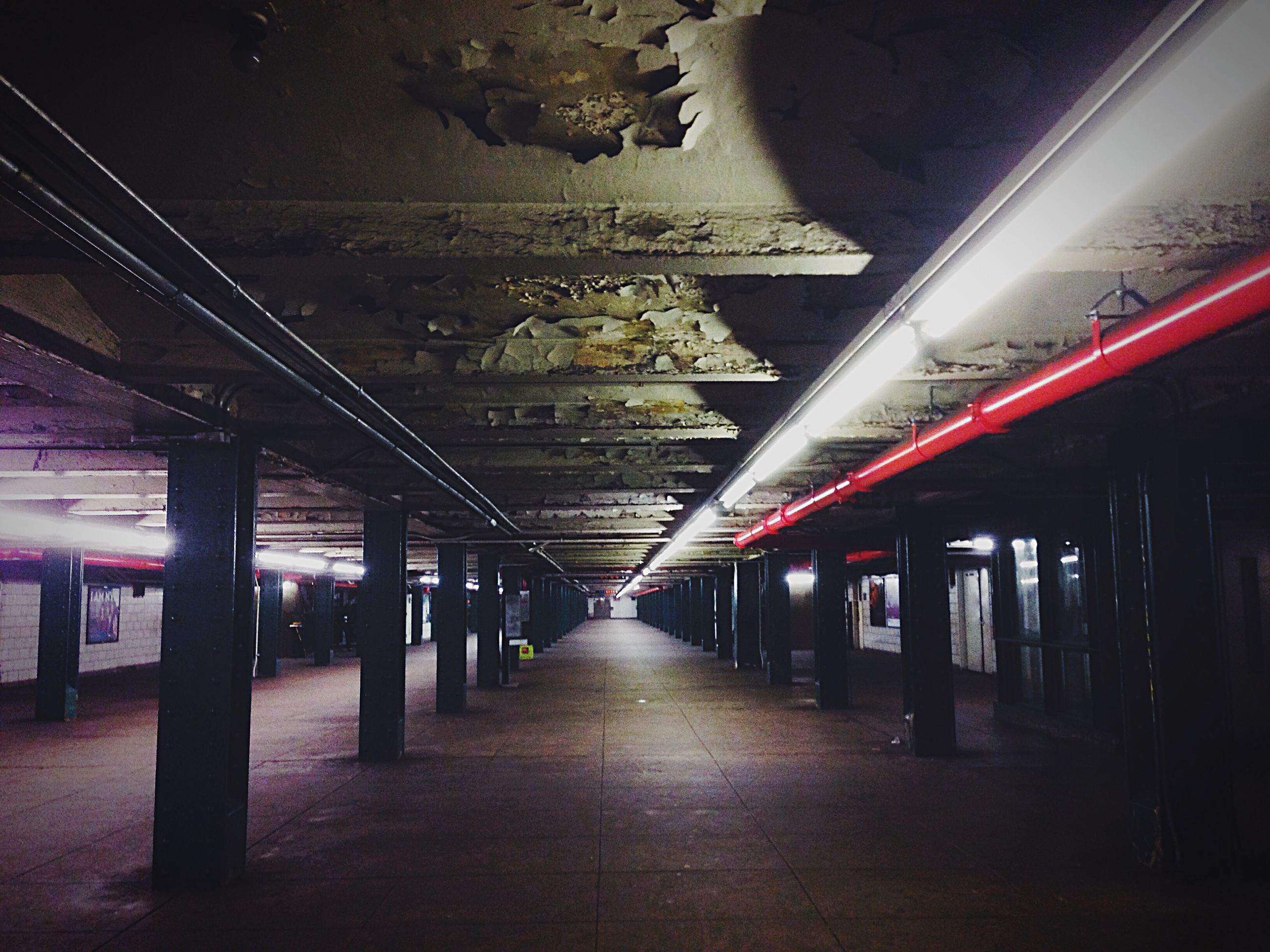 indoors, ceiling, illuminated, the way forward, architecture, built structure, transportation, diminishing perspective, empty, architectural column, lighting equipment, corridor, railroad station platform, vanishing point, long, flooring, railroad station, interior, column, subway