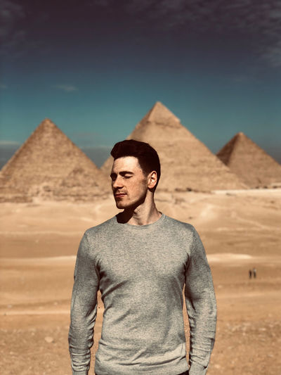 Young man standing in desert against sky