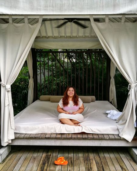 Portrait of smiling woman sitting on outdoor bed at luxury hotel