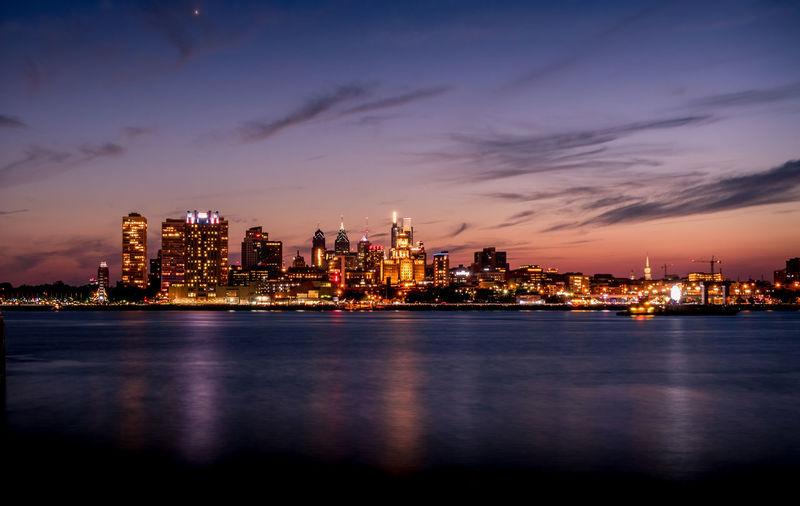 Illuminated buildings by sea against sky at dusk