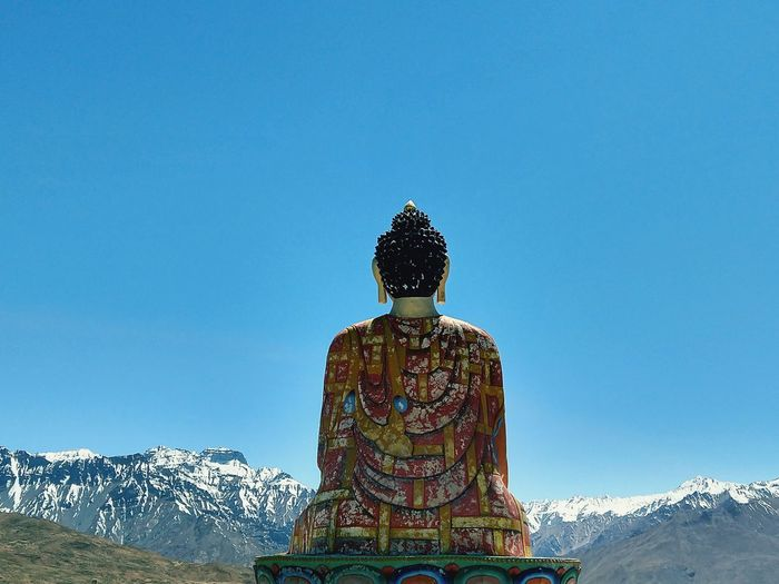 Buddha statue against snowcapped mountains and clear sky