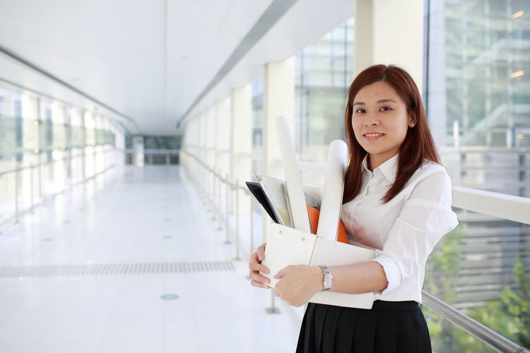 Portrait of young woman holding box while standing in office corridor