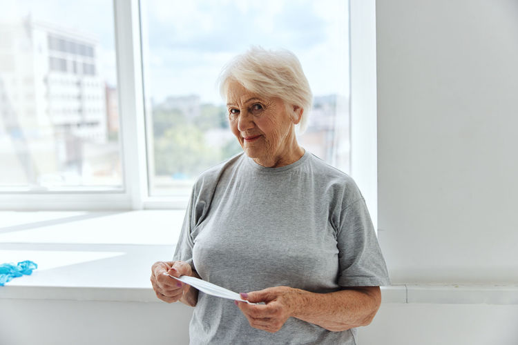 Mid adult woman standing against window at home
