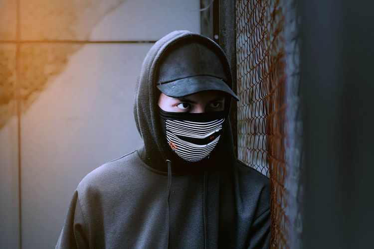 Close-up of man wearing mask and cap