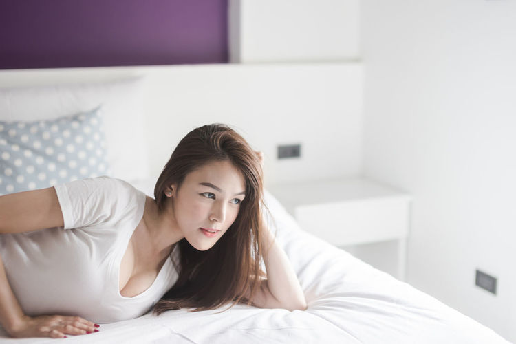 Adult Beautiful Woman Beauty Bed Bedroom Contemplation Domestic Room Furniture Hair Hairstyle Indoors  Lifestyles Long Hair Lying Down One Person Portrait Real People Relaxation White Color Women Young Adult Young Women