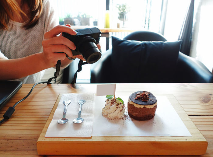 Shoot first eat later, a woman taking photo of chocolate mousse cake by digital camera in a cafe Shoot First Eat Later Moussecake Chocolate Cake Cafe Bakery Dessert Sweet Social Issues Photography Food Urban Lifestyle Digital Camera Young Woman Leisure Mousse Take Photo Hand Restaurant Wooden Table