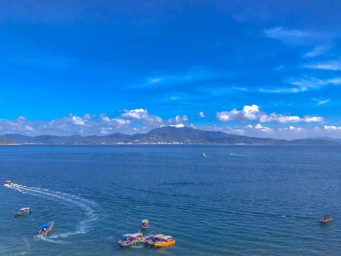 People on sea against blue sky