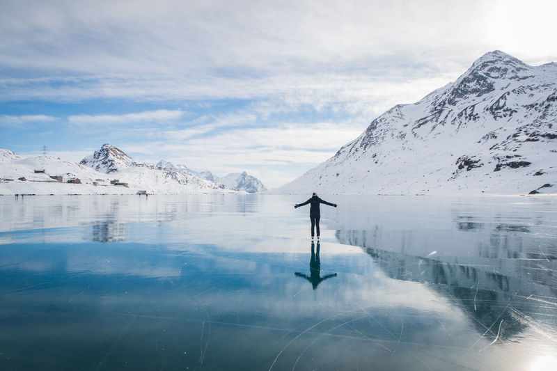 Woman Standing On Frozen Lake By Snowcapped Mountain Against Cloudy Sky