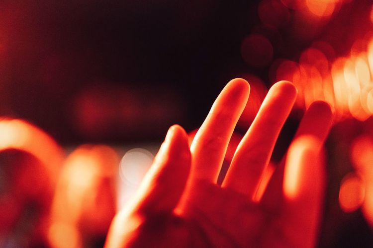 Close-Up Of Human Hand Against Illuminated Defocused Lights At Night