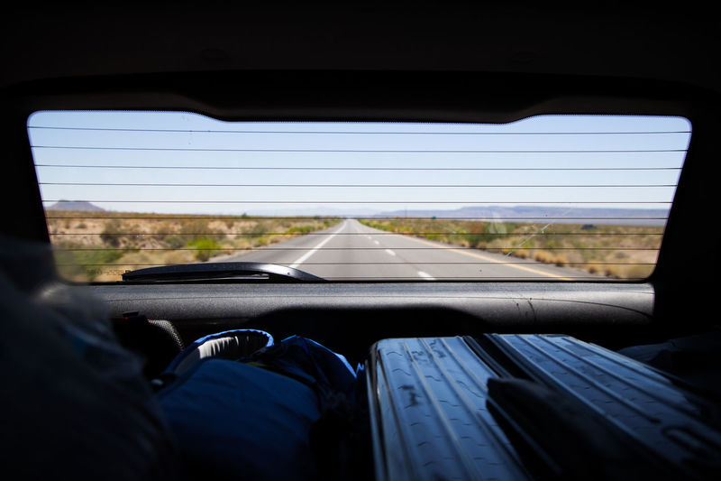 Road seen through rear windshield of car