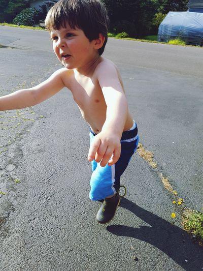Shirtless Boy Running On Road