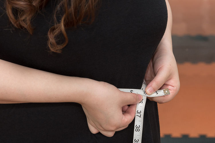 Midsection of woman measuring waist with tape