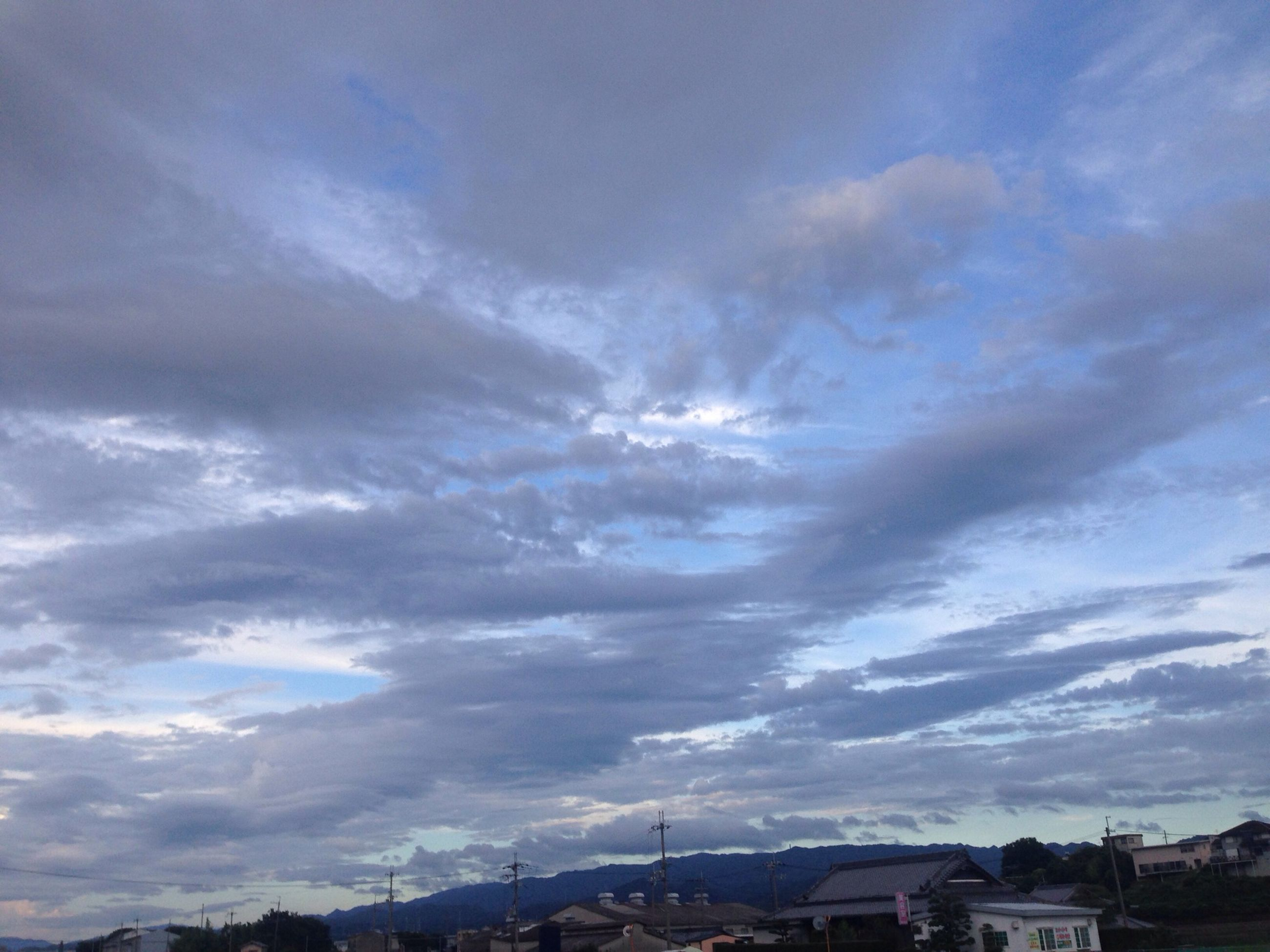 sky, cloud - sky, building exterior, built structure, architecture, cloudy, scenics, mountain, beauty in nature, cloud, nature, house, weather, tranquil scene, tranquility, landscape, town, outdoors, city, blue