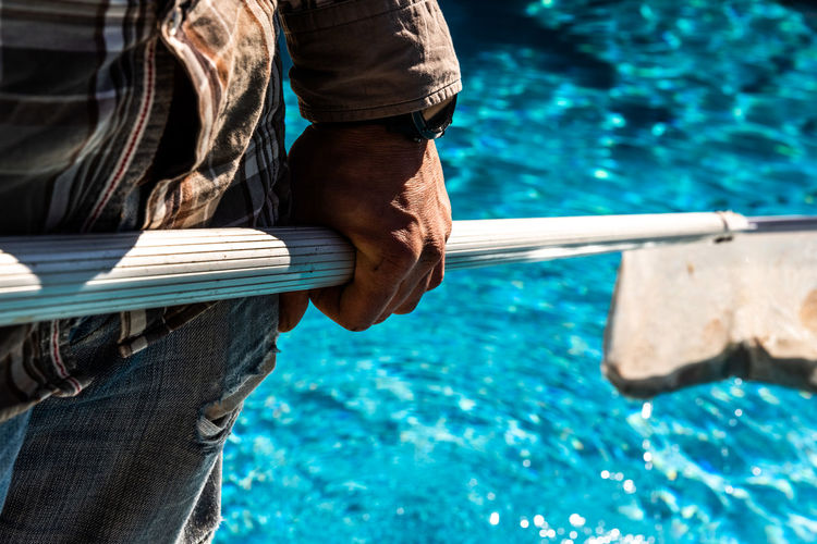 Midsection of man holding netting while standing by swimming pool