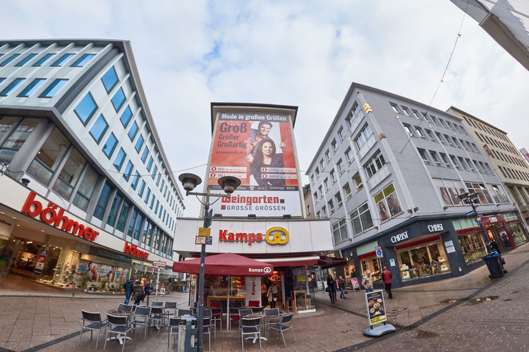 ESSEN, GERMANY - MARCH 07, 2016: Few pedestrants walk through a shopping street after rain Adult Adults Only Architecture Architecture Building Exterior Built Structure City City Life City Street Close-up Crowd Day Downtown Downtown District Essen Germany Neon Outdoors People Shopping Mall Sky Store Travel Destinations Urban Urban Skyline