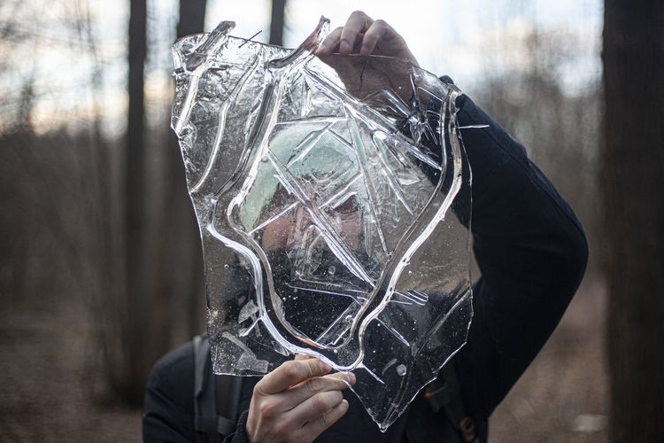 Man holding ice while standing outdoors during winter