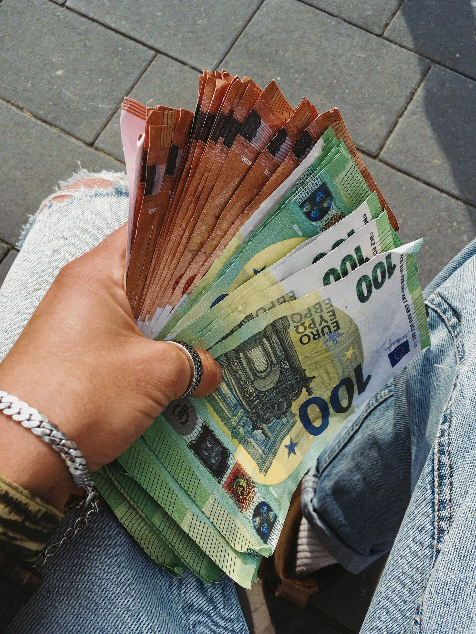 paper currency, cash, currency, one person, hand, finance, holding, high angle view, fashion accessory, money, personal perspective, business, clothing, watch, wealth, adult, lifestyles, leisure activity, art, close-up