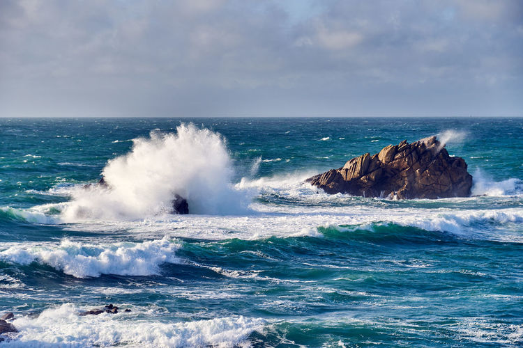 Waves of the atlantic ocean break on a rock with splashing gout on quiberon in brittany in france