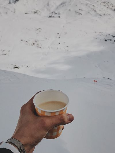 Close-Up Of Cropped Hand Holding Coffee Cup At Snowcapped Mountain