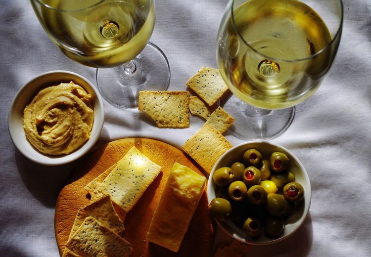 High Angle View Of White Wine With Food On Table