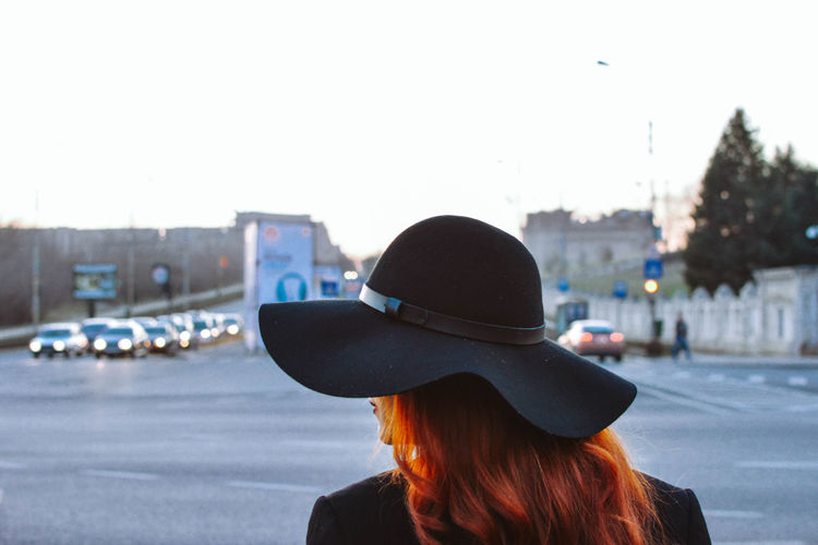 Rear view of woman wearing hat standing on road against sky in city