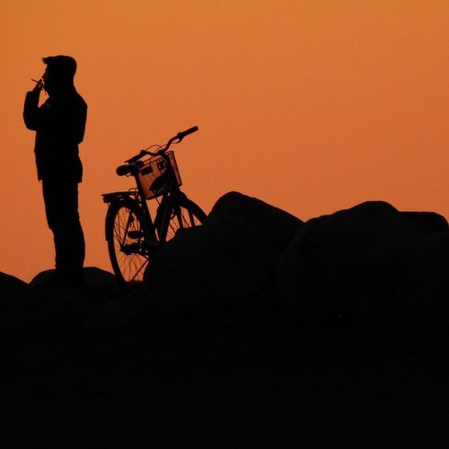 Silhouette man riding bicycle on cliff during sunset
