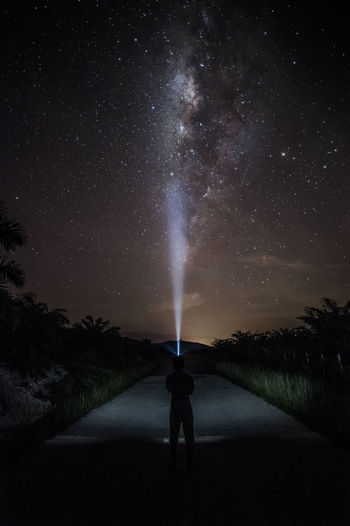 Astronomy Beauty In Nature Direction Flashlight Full Length Lifestyles Milky Way Nature Night One Person Plant Real People Rear View Road Scenics - Nature Sky Space Standing Star - Space The Way Forward Tree