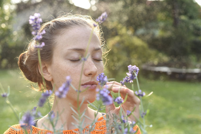 young woman gardening Beauty In Nature Day Eyes Closed  Field Flower Focus On Foreground Fragility Freshness Front Or Back Yard Headshot Holding Leisure Activity Lifestyles Motion Nature One Person Outdoors Petal Plant Real People Scented Smelling Sunlight Young Adult Young Women