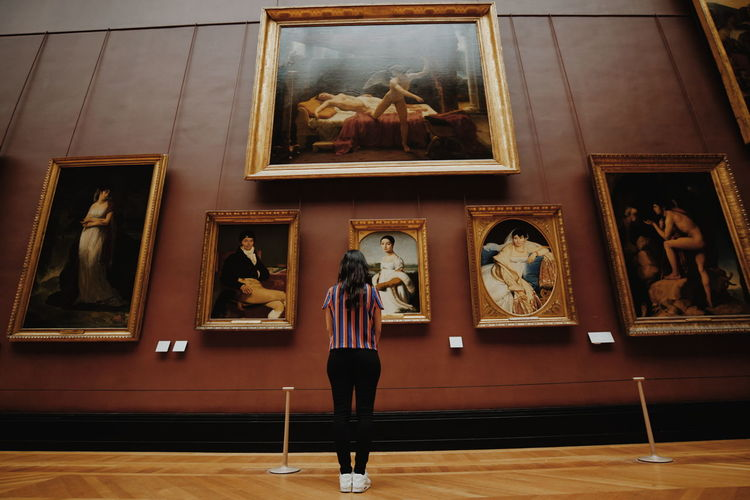 Midsection of woman photographing in museum