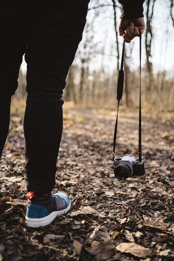 A person holding a vintage photo camera on a strap while walking through the woods in the fall.